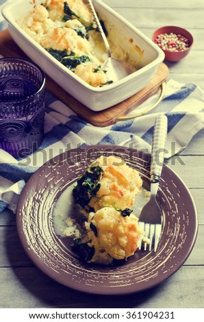 Casserole with cauliflower and spinach on a wooden background. Selective focus. - stock photo