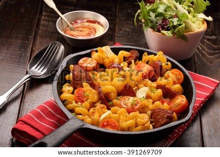 Casserole with chorizo sausage in a frying pan on wooden background