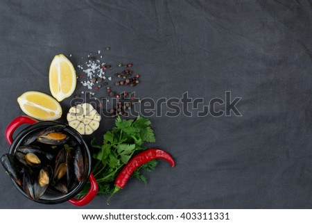 Casserole with mussels, lemons, chili pepper and spices - stock photo