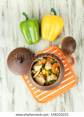 Casserole with vegetables and meat on potholder, on wooden background - stock photo