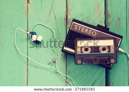 Cassette and old tape player over wooden background. retro filter - stock photo