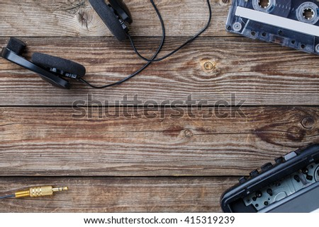 Cassette tape, cassette player and headphones over wooden table. top view. - stock photo
