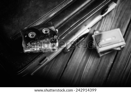 Cassette tape lying on an old suitcase. Black and white. - stock photo