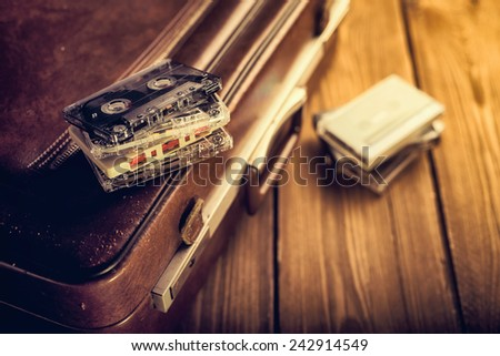Cassette tape lying on an old suitcase. Vintage Retouching - stock photo