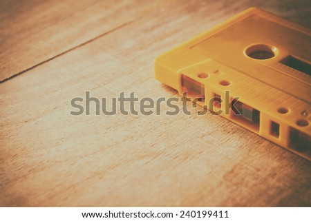 Cassette tape over wooden table. image is instagram style filtered.  - stock photo