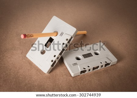 cassette tapes with pencil for rewind on brown paper background. Vintage style - stock photo