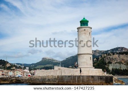 CASSIS, FRANCE - MAY 14: Lighthouse of Cassis, marina and citadel on the hill at backgrounds as seen on May 14, 2013 in Cassis, France. Cassis is a gateway to famous Calanques national park.
