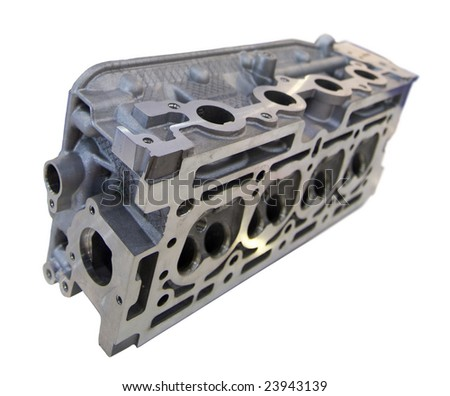 Cast and milled iron engine block with four cylinders and four valves per cylinder. Isolated on white. Shallow depth of field with the nearest part of the engine in focus. - stock photo