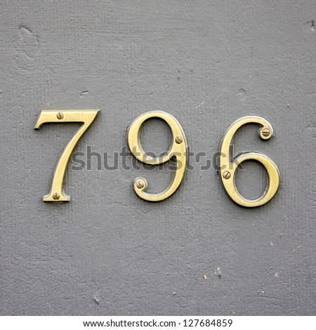 cast bronze house number seven hundred and ninety-six on a gray wall - stock photo