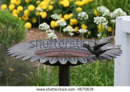 Cast Iron Bird Bath In A Flower Garden.