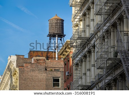 Cast iron facades of Soho loft buildings and rooftop wooden water tank, in Downtown Manhattan, New York City - stock photo
