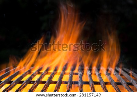 Cast-iron grate with fire flames, ready to add some meat. - stock photo