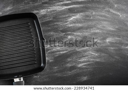 Cast iron griddle pan on black background - stock photo