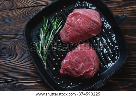 Cast-iron grill with two raw beef fillet mignon steaks, top view - stock photo