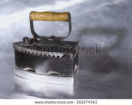 Cast iron iron on a metal background - stock photo