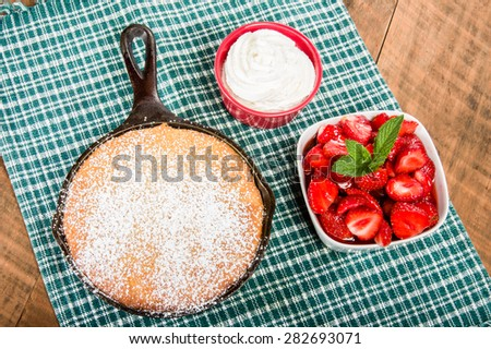 Cast iron skillet baked cake with bowl of red strawberries - stock photo