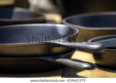 Cast iron skillets, two, sitting next to other skillets on a wooden table. - stock photo