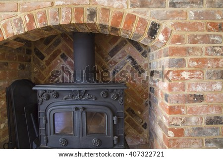 Cast iron stove inside a stone arch fireplace - stock photo