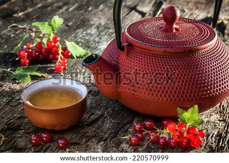 Cast iron teapot and clay cup with redcurrants on old wooden table. - stock photo