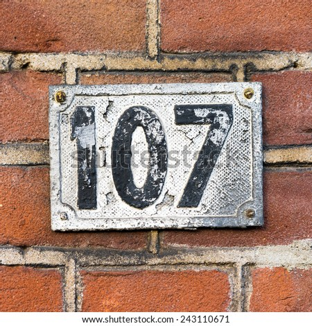 cast metal house number on a red brick wall - stock photo