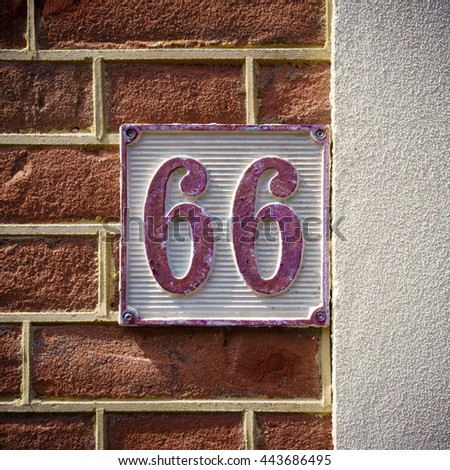 cast metal house number sixty six, painted red and white - stock photo