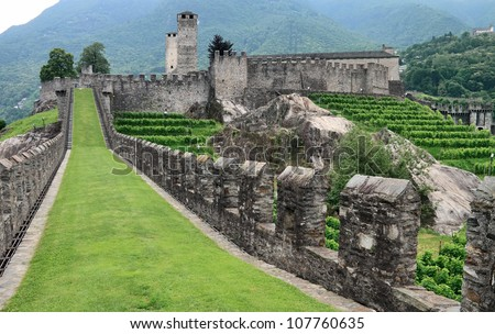 Castelgrande, seen from the west with the massive wall Murata in the foreground, Bellinzona, Switzerland. - stock photo