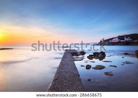 Castiglioncello travel destination, concrete pier in the bay, rocks and sea on sunset. Tuscany, Italy, Europe. Long Exposure - stock photo