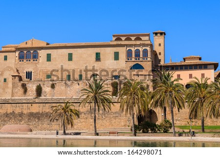 Castle building near La Seu Cathedral  building and palm trees in front in Palma de Majorca, Spain - stock photo