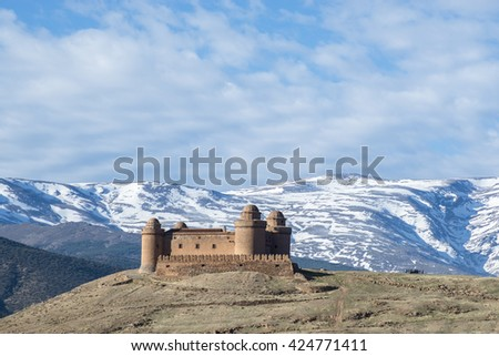 Castle  Calahorra with the snow capped mountains of the Sierra Nevada, La Calahorra, Gaudix, Granada Province, Andalusia, Spain. - stock photo