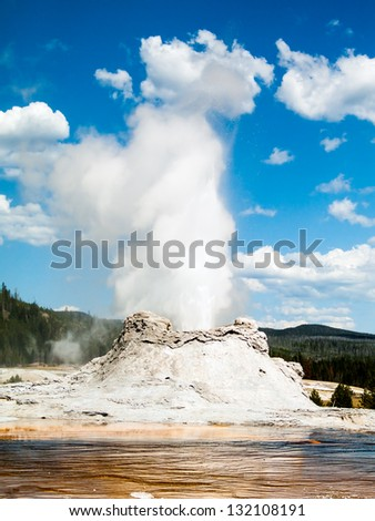 Castle Geyser erupts in the Upper Geyser Basin of Yellowstone National Park, Wyoming, USA. Castle Geyser is in the Upper Geyser Basin of Yellowstone not far from Old Faithful Geyser. - stock photo