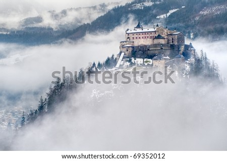 Castle Hohenwerfen by Salzburg high over clouds on a misty mountain in the Alps - stock photo