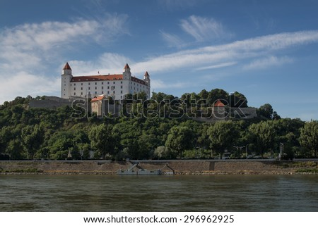 Castle in Bratislava, Slovakia View on a castle in Bratislava, located on the top of the hill. River Danube in the foreground. Blue sky with white clouds.  - stock photo