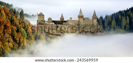 Castle in the high mountains with fog fall - stock photo