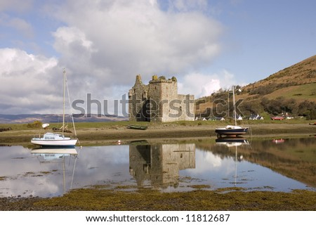 Castle Lochranza on the island of Arran in Scotland with boats reflected in the surrounding water