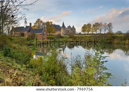 Castle Muiderslot, The Netherlands. A lake on the foreground. Blue sky with clouds and buildings reflecting in the water.