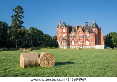 Castle of la Grillere in Chatel de Neuvre, Auvergne, France, with hays on the lawn in the morning - stock photo