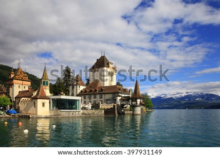 Castle of Oberhofen with lake of Thun and snowy mountains, Switzerland
