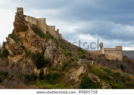"Castle of ""Roccascalegna"" perched over a cliff in Italian countryside in a cold morning"