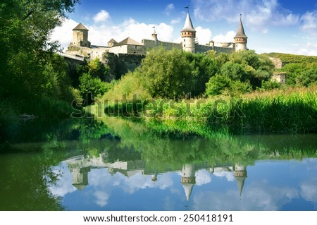Castle on the hill and its reflection in water - stock photo