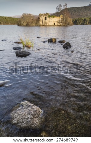 Castle ruins on Loch an Eilein in the Cairngorm National Park in Scotland. - stock photo