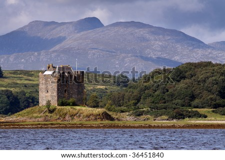 Castle Stalker is an authentic medieval tower house situated on an islet on Loch Laich on the north-west coast of Scotland amidst some truly spectacular mountain scenery. - stock photo