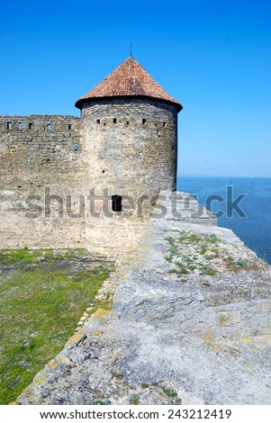 castle tower with a slate roof on a background of blue sky and sea