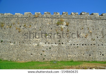 castle wall green grass blue sky - stock photo