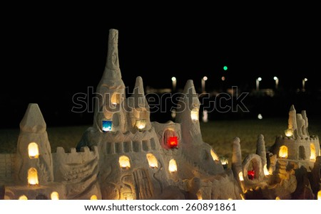 Castle with candles made from sand on the beach. - stock photo