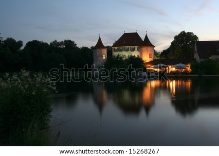 Castle with restaurant in front of a calm lake at dusk. - stock photo