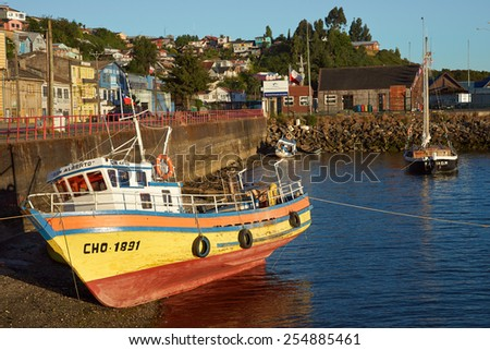 CASTRO, CHILE - JANUARY 15, 2015: Colourful fishing boat resting on the shore in Castro, capital of the Island of Chiloe in Chile. - stock photo