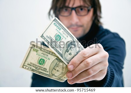Casual adult man is paying in dollar bills, corruption and bribe concept.