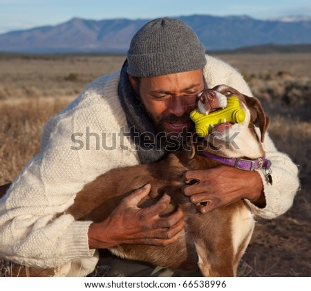 Casual African American man hugging and playing with his dog. - stock photo