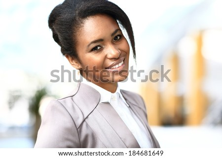 Casual african business woman looking happy and smiling - stock photo