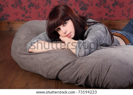 Casual and relaxed a beautiful young caucasian girl wearing blue jeans and knitted top, lying on a bean bag at home on the floor. - stock photo